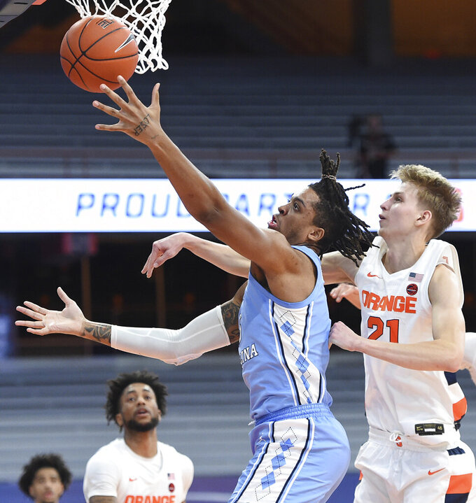 North Carolina forward Armando Bacot, front left, goes for the basket past Syracuse forward Marek Dolezaj (21) during an NCAA college basketball game in Syracuse, N.Y., Monday, March 1, 2021. (Dennis Nett/The Post-Standard via AP)