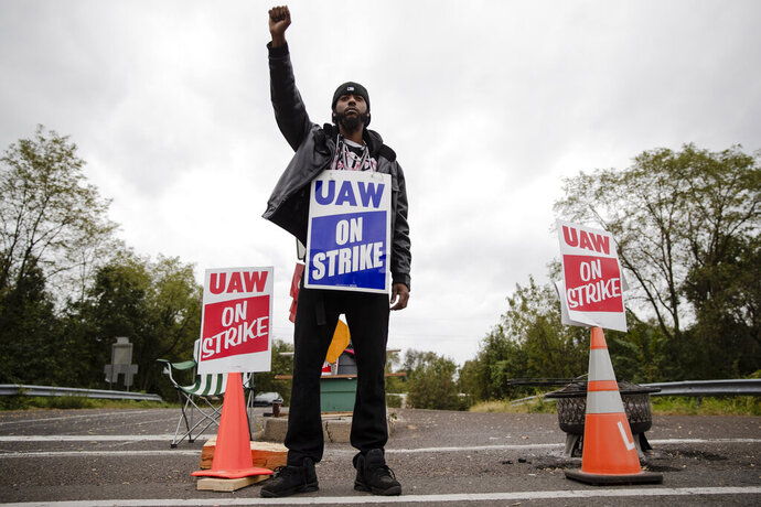 Ryan Piper with the United Auto Workers continues to picket after news of a tentative contract agreement with General Motors, in Langhorne, Pa., Wednesday, Oct. 16, 2019. Bargainers for General Motors and the United Auto Workers reached a tentative contract deal on Wednesday that could end a monthlong strike that brought the company's U.S. factories to a standstill. (AP Photo/Matt Rourke)