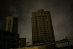 In this May 23, 2019 photo, only two apartments of a building are illuminated by electric generators during a black out in Maracaibo, Venezuela. Some have opted for small generation units costing a few hundred dollars that can pump out enough power to run a few appliances at a time, such as using the lights and water heater for a shower. (AP Photo/Rodrigo Abd)