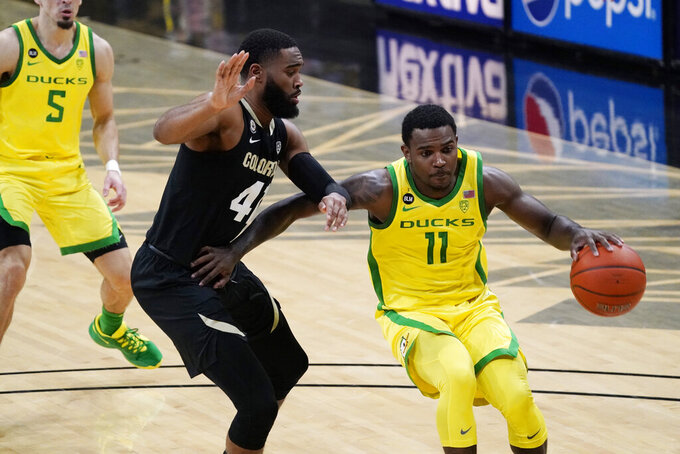 Oregon guard Amauri Hardy, right, drives past Colorado forward Jeriah Horne in the first half of an NCAA college basketball game Thursday, Jan. 7, 2021, in Boulder, Colo. (AP Photo/David Zalubowski)