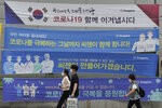"""People wearing face masks pass by banners hoping to overcome the COVID-19 crisis on a street in Seoul, South Korea, Tuesday, July 13, 2021. South Korea's streak of more than 1,000 daily coronavirus cases has reached a week as health authorities scramble to slow a viral surge that has brought Seoul's thriving nightlife to a standstill and professional baseball to a halt. The signs on posters read """"Let's overcome the COVID-19."""" (AP Photo/Ahn Young-joon)"""