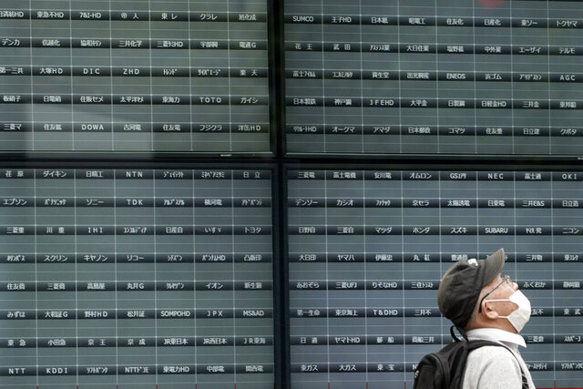 A man walks past a blank electronic stock board supposedly showing Japan's Nikkei 225 index at a securities firm in Tokyo Thursday, Oct. 1, 2020. Trading on the Tokyo Stock Exchange was suspended Thursday because of a problem in the system for relaying market information. (AP Photo/Eugene Hoshiko)