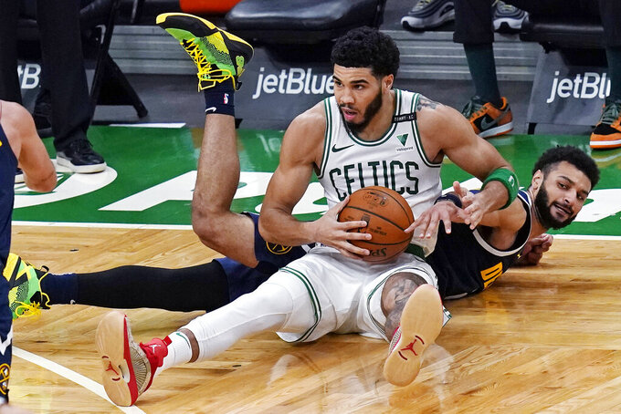 Denver Nuggets guard Jamal Murray, right, stretches for the ball as Boston Celtics forward Jayson Tatum, center, gains control during the first half of an NBA basketball game, Tuesday, Feb. 16, 2021, in Boston. (AP Photo/Charles Krupa)