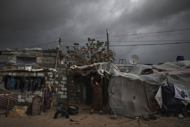 A Palestinian woman checks the nylon cover on the roof of her house on a rainy day in a poor neighborhood of Khan Younis, in the southern Gaza Strip, Wednesday, Jan. 20, 2021. (AP Photo/Khalil Hamra)