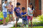 Jesse Yip, center, plays with his sister, Kelsey, right, and brother Toby, left, as their parents Vicky Li and Patrick Yip watch outside their home, Friday, July 10, 2020, in Houston. Vicky Li Yip works from home and says online schooling has been exhausting, even with her husband helping out. But with her city becoming a national hot spot, she has been considering what it would mean for her children to face possible exposure every day. (AP Photo/David J. Phillip)
