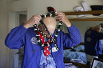 Don Long puts on a number of leis while getting dressed at his home Friday, Dec. 7, 2018, in Napa, Calif., before driving to attend a number of Pearl Harbor remembrances. Retired U.S. Navy Cmdr. Don Long wasn't at Pearl Harbor when Japanese war planes started bombing Hawaii on December 7, 1941, he was on the opposite side of Oahu standing watch aboard an anchored military seaplane in Kaneohe Bay. But the wave of bombs and bullets reached his military installation soon after Pearl Harbor was struck, and the young sailor watched from afar as buildings and planes started to explode all around him. On the 77th anniversary of the attack, Long will remember from his home where the 97-year-old survivor will reflect and honor those who died. (AP Photo/Eric Risberg)