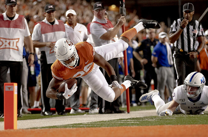 Kansas linebacker Gavin Potter (19) trips Texas running back Keaontay Ingram (26) during an NCAA college football game Saturday, Oct. 19, 2019, in Austin, Texas. (Nick Wagner/Austin American-Statesman via AP)