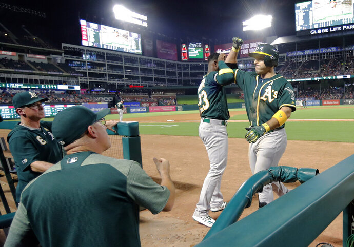 Oakland Athletics' Jurickson Profar (23) greets Ramon Laureano, right, at the top of the dugout after Laureano hit a three-run home run against the Texas Rangers during the sixth inning of a baseball game in Arlington, Texas, Friday, Sept. 13, 2019. (AP Photo/Tony Gutierrez)