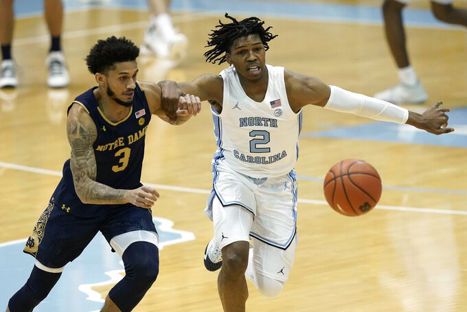 Notre Dame guard Prentiss Hubb (3) and North Carolina guard Caleb Love (2) chase the ball during the first half of an NCAA college basketball game in Chapel Hill, N.C., Saturday, Jan. 2, 2021. (AP Photo/Gerry Broome)