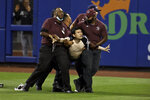 A fan is carried by security guards after running onto the field during the sixth inning of a baseball game between the New York Yankees and the New York Mets on Saturday, Sept. 11, 2021, in New York. (AP Photo/Adam Hunger)