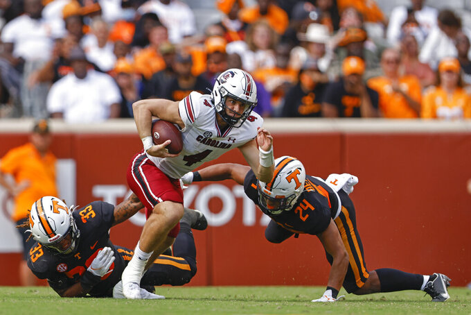 South Carolina quarterback Luke Doty (4) escapes from Tennessee linebackers Jeremy Banks (33) and Aaron Beasley (24) during the second half of an NCAA college football game Saturday, Oct. 9, 2021, in Knoxville, Tenn. Tennessee won 45-20. (AP Photo/Wade Payne)