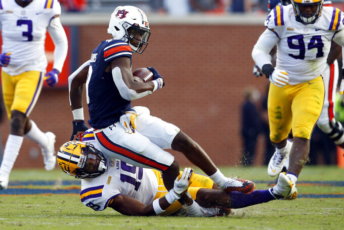 Auburn wide receiver Seth Williams (18) is tackled by LSU linebacker Jabril Cox (19) after a reception during the second half of an NCAA college football game on Saturday, Oct. 31, 2020, in Auburn, Ala. (AP Photo/Butch Dill)