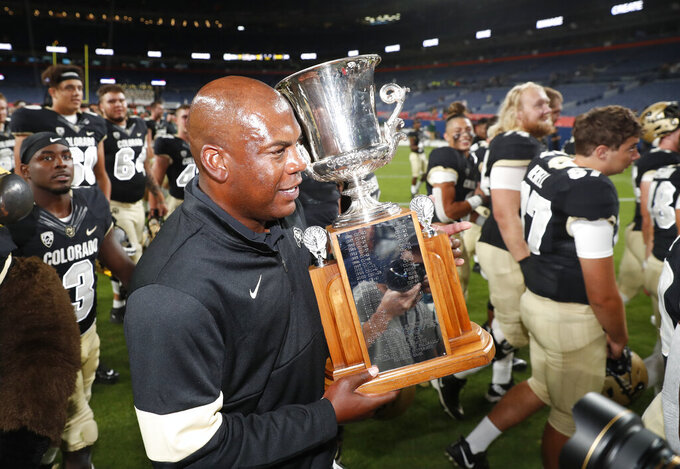 Colorado head coach Mel Tucker carries the Centennial Cup after his team beat intrastate rival Colorado State in an NCAA college football game Friday, Aug. 30, 2019, in Denver. Colorado won 52-31. (AP Photo/David Zalubowski)