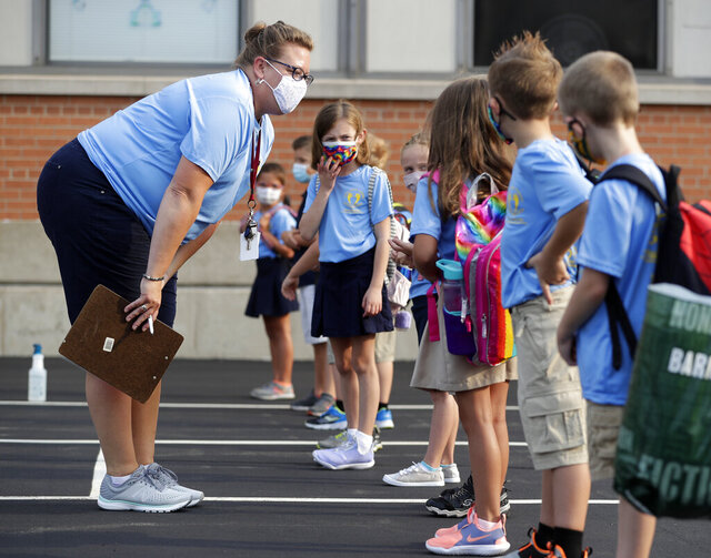 FILE - In this Aug. 26, 2020 file photo, first-grade teacher Jessica Johnson asks students if they've been sick or near anyone who's been sick before the start of the first day of school at Our Lady of Lourdes Catholic School, in De Pere, Wis. Gov. Tony Evers has extended Wisconsin's mask mandate until Nov. 21, citing a surge in coronavirus cases across the state.  (Sarah Kloepping/The Post-Crescent via AP)