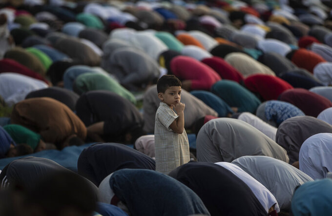 Palestinian Muslims attend the prayer of the first day of Eid al-Adha in Gaza City, Tuesday, July. 20, 2021. (AP Photo/Khalil Hamra)