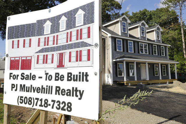 FILE - In this Sept. 3, 2019, file photo a for sale sign, left, rests in front of a newly constructed home, in Norwood, Mass. On Wednesday, Feb. 19, 2020, the Commerce Department reports on U.S. home construction in January. (AP Photo/Steven Senne, File)