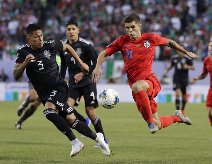 United States midfielder Christian Pulisic, right, controls the ball against Mexico defender Carlos Salcedo during the first half of the CONCACAF Gold Cup final soccer match at Soldier Field in Chicago, Sunday, July 7, 2019. (AP Photo/Nam Y. Huh)