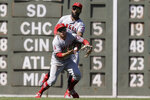 Los Angeles Angels' Brian Goodwin, behind, catches a fly ball by Boston Red Sox's Chris Owings as Angels' David Fletcher, front, scrambles in the sixth inning of a baseball game at Fenway Park, Sunday, Aug. 11, 2019, in Boston. (AP Photo/Steven Senne)