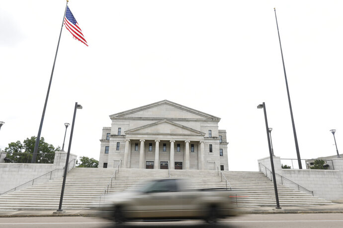 The Mississippi state flag was missing from its pole to the right of the American flag, outside the Carroll Gartin Justice Building in Jackson, Miss., Monday, June 29, 2020, the day after both chambers of the state Legislature passed a bill to take down and replace the current flag, which contains the Confederate battle emblem. (AP Photo/Rogelio V. Solis)