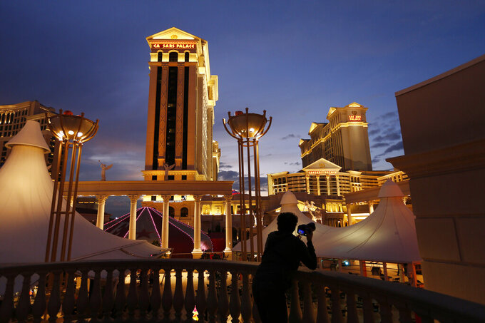 FILE - In this Jan. 12, 2015, file photo, a man takes pictures of Caesars Palace hotel and casino, in Las Vegas. Las Vegas is not worried about the competition from casinos in other states that for the first time Sunday, Feb. 3, 2019, will also offer football fans a chance to bet on the Super Bowl. The weekend is worth hundreds of millions of dollars to the city, which draws tens of thousands of people for the big game's weekend.(AP Photo/John Locher, File)