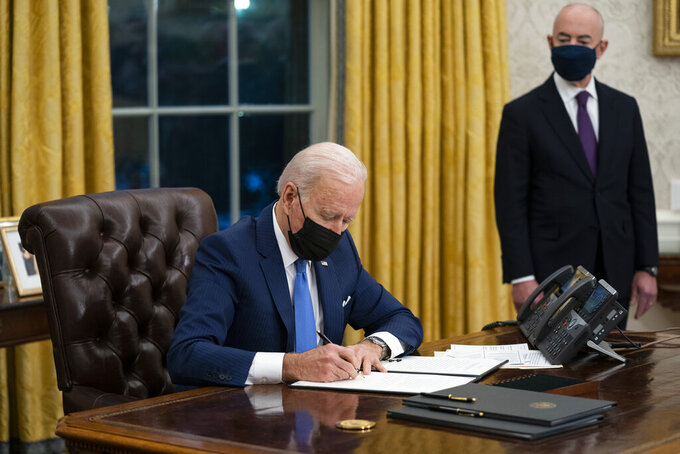 FILE - In this Feb. 2, 2021, file photo, Secretary of Homeland Security Alejandro Mayorkas looks on as President Joe Biden signs an executive order on immigration, in the Oval Office of the White House in Washington.  (AP Photo/Evan Vucci, File)