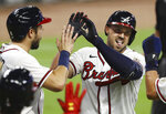 Atlanta Braves' Adam Duval, right, is greeted at home by Travis d'Arnaud, left, after hitting a grand slam, his third homer of the night, for a 29-9 lead over the Miami Marlins during the seventh inning of a baseball game Wednesday, Sept. 9, 2020, in Atlanta. (Curtis Compton/Atlanta Journal-Constitution via AP)