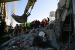 Rescuers search at a damaged building after a magnitude 6.4 earthquake in Thumane, western Albania, Tuesday, Nov. 26, 2019. Rescue crews used excavators to search for survivors trapped in toppled apartment buildings Tuesday after a powerful pre-dawn earthquake in Albania killed at least 14 people and injured more than 600. (AP Photo/Visar Kryeziu)
