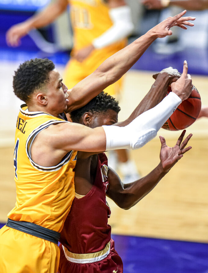 Elon guard Darius Burford (12) is fouled by Drexel guard Xavier Bell (4) as he grabs a rebound during the first half of an NCAA college basketball game for the Colonial Athletic Association men's tournament championship in Harrisonburg, Va., Tuesday, March 9, 2021. (AP Photo/Daniel Lin)