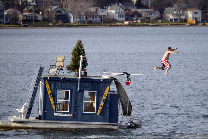 FILE - In this Dec. 24, 2015 file photo, a man jumps into Pontoosuc Lake in Pittsfield, Mass. The New England lake is typically frozen in December, but unusually warm temperatures have kept the water open. On Thursday, Oct. 18, 2018, the National Weather Service forecasted a warmer than normal 2018-2019 winter for the northern and western three-quarters of the U.S. (Ben Garver/The Berkshire Eagle via AP)