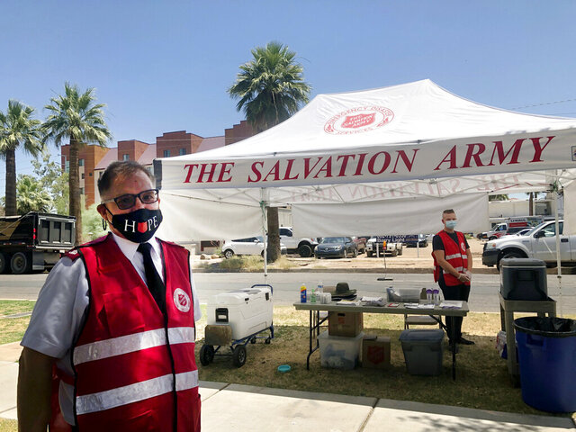 Salvation Army Maj. David Yardley, left, stands outside the Salvation Army Phoenix downtown headquarters where a heat relief station was set up on Thursday, May 28, 2020, in Phoenix, Ariz. A heat relief station offering cold water and a cool place inside to rest out of the brutal sun will be open every day through Sunday while an excessive heat warning is in effect. (AP Photo/Anita Snow)