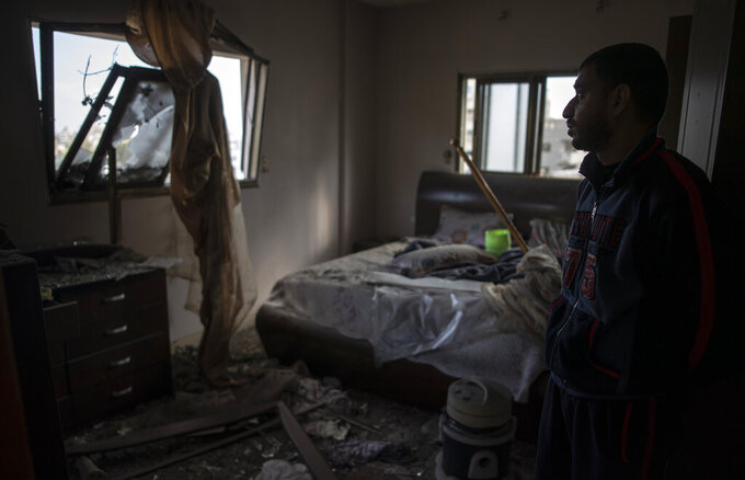 A Palestinian man looks at his damaged bedroom following early morning Israeli airstrikes on Gaza City, Tuesday, May 18, 2021. Israel carried out a wave of airstrikes on what it said were militant targets in Gaza, leveling a six-story building in downtown Gaza City, and Palestinian militants fired dozens of rockets into Israel early Tuesday, the latest in the fourth war between the two sides, now in its second week. (AP Photo/Khalil Hamra)