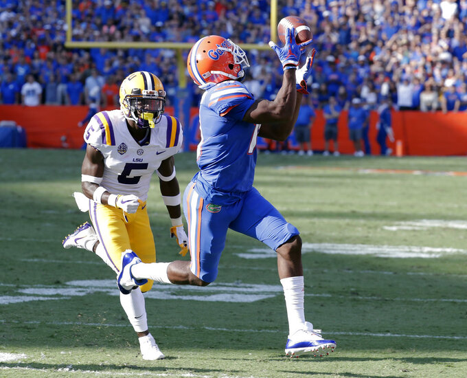 Florida wide receiver Josh Hammond, right, catches a 35-yard pass in front of LSU cornerback Kary Vincent Jr., left, to set up a Florida touchdown in the first half of an NCAA college football game, Saturday, Oct. 6, 2018, in Gainesville, Fla. (AP Photo/John Raoux)