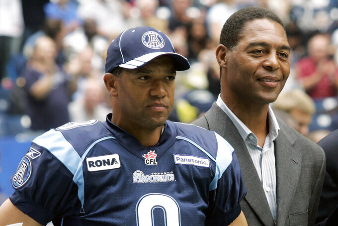 """FILE - Toronto Argonauts Damon Allen, left, and his brother Marcus Allen stand on the sidelines before a Canadian Football League football game against the Hamilton Tiger-Cats in Toronto, in this Saturday, Sept. 9, 2006, file photo. Three words resonate with Damon Allen when thinking of what his brother and NFL legend Marcus told him on multiple occasions during his storied career in the Canadian Football League. """"Play within yourself,"""" Allen said. Now, Allen is hoping to share those words and his vast knowledge from a Hall of Fame career in the CFL with the Las Vegas Raiders, the organization his older brother starred for and led to a Super Bowl title in 1984. (Nathan Denette/Canadian Press via AP)"""