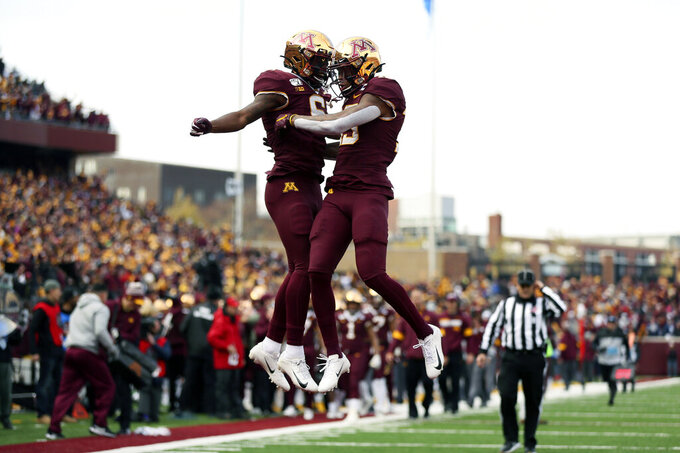 Minnesota wide receiver Rashod Bateman, right, jumps up in celebration with teammate Tyler Johnson after Bateman scored a touchdown against Penn State during an NCAA college football game Saturday, Nov. 9, 2019, in Minneapolis. (AP Photo/Stacy Bengs)