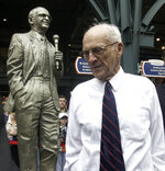 FILE - In this Sept. 15, 2002 file photo, Detroit Tigers Hall of Fame broadcaster Ernie Harwell pauses near a statue honoring him that was unveiled inside the entrance to Comerica Park in Detroit. Their voices are the backdrop to all those warm summer nights. Their distinctive calls are part of the game's lore. Fans visualize the action through their stories and descriptions. (AP Photo/Paul Sancya, File)