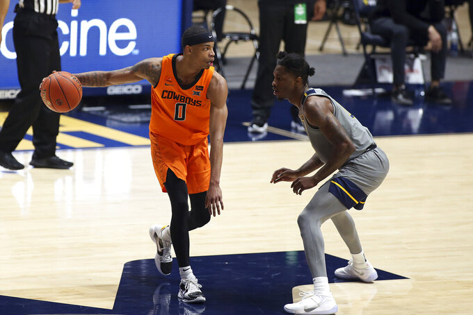 Oklahoma State guard Avery Anderson III (0) is defended by West Virginia guard Kedrian Johnson (0) during the second half of an NCAA college basketball game Saturday, March 6, 2021, in Morgantown, W.Va. (AP Photo/Kathleen Batten)
