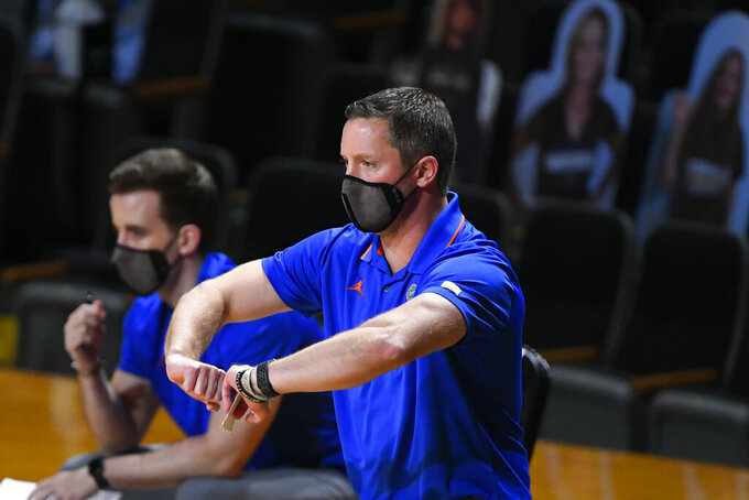 Florida coach Mike White motions to players during the first half of the team's NCAA college basketball game against Vanderbilt, Wednesday, Dec. 30, 2020, in Nashville, Tenn. (AP Photo/John Amis)