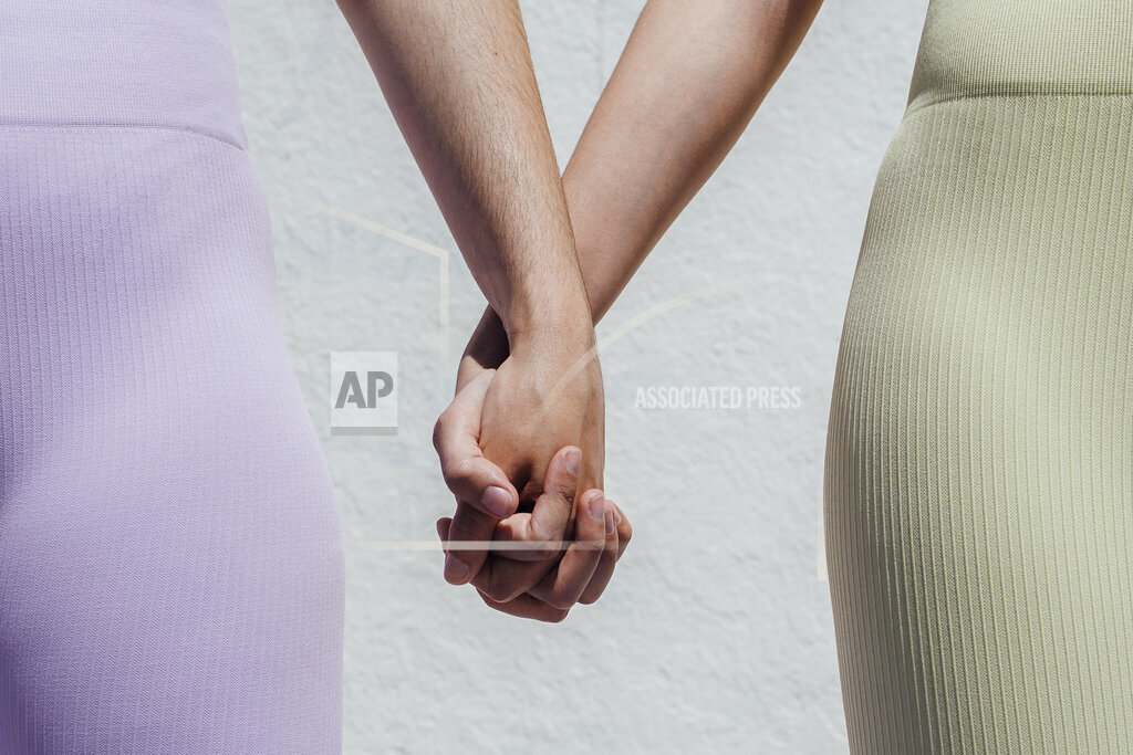 Sportswomen holding hands while standing in front of wall