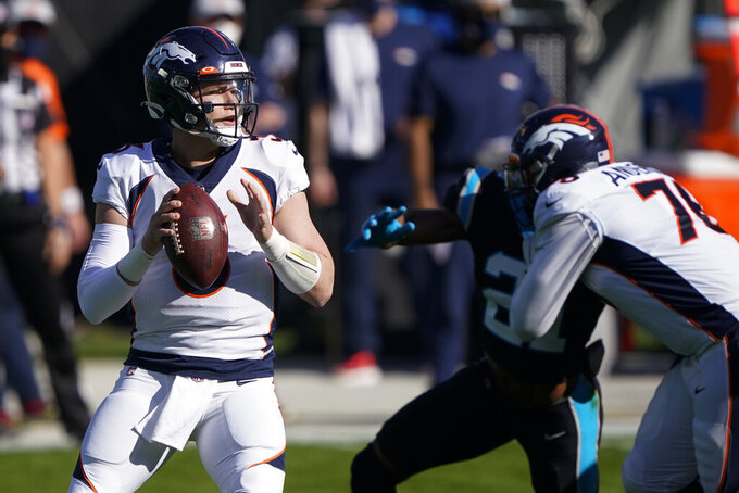 Denver Broncos quarterback Drew Lock looks to pass against the Carolina Panthers during the first half of an NFL football game Sunday, Dec. 13, 2020, in Charlotte, N.C. (AP Photo/Brian Blanco)