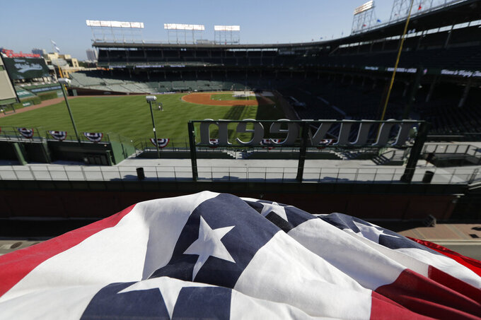 Wrigley Field is viewed from nearby rooftop before an opening day baseball game between the Chicago Cubs and the Milwaukee Brewers in Chicago, Friday, July 24, 2020, in Chicago. For fans looking to see major league baseball live during the coronavirus pandemic, there are few options besides the rooftops along Waveland and Sheffield Avenues. (AP Photo/Nam Y. Huh)