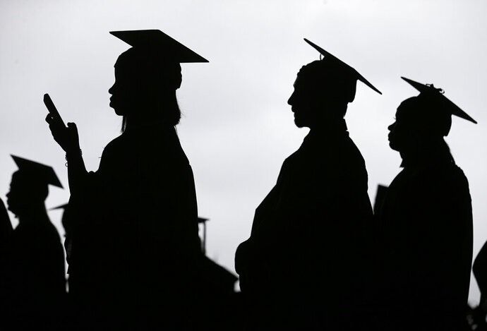 FILE - In this May 17, 2018, file photo, new graduates line up before the start of the Bergen Community College commencement at MetLife Stadium in East Rutherford, N.J. Americans who have spent time in foster care are far more likely than other adults to lack a college degree, health insurance and a stable health care provider, according to a new federal analysis released Wednesday, Jan. 22, 2020, that is unprecedented in its scope.  (AP Photo/Seth Wenig, File)