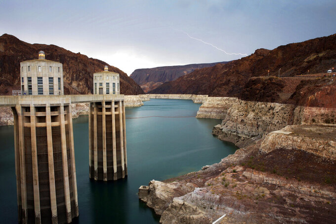 FILE - In this July 28, 2014, file photo, lightning strikes over Lake Mead near Hoover Dam that impounds Colorado River water at the Lake Mead National Recreation Area in Arizona. Two major California water agencies have settled a lawsuit that once threatened to derail a multi-state agreement to protect a river that serves millions of people in the U.S. West. The agencies announced Monday, Sept. 20, 2021, they have reached a settlement that resolves both lawsuits. (AP Photo/John Locher, File)