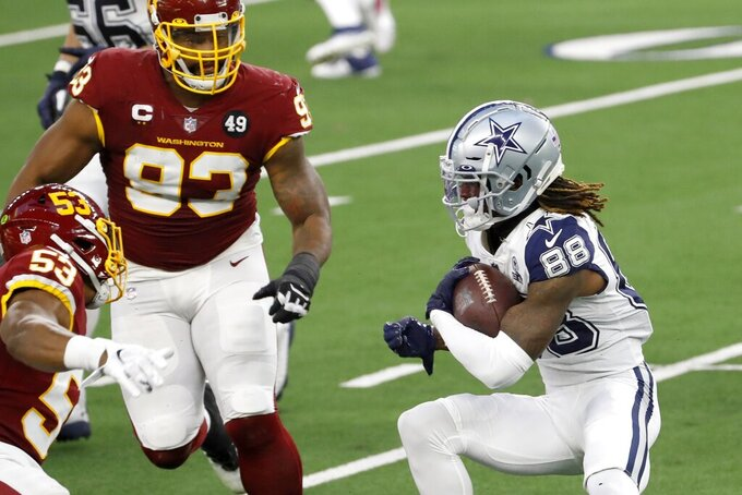Dallas Cowboys wide receiver CeeDee Lamb (88) looks for running room as Washington Football Team's Jon Bostic (53) and Jonathan Allen (93) move to make the stop in the first half of an NFL football game in Arlington, Texas, Thursday, Nov. 26, 2020. (AP Photo/Roger Steinman)