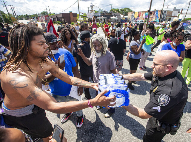 A Greensboro Police officer hands protesters a case of water in the intersection of Gate City Blvd. and Eugene Street in Greensboro, N.C. on Saturday, May 30, 2020. (Woody Marshall/News & Record via AP)