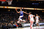 Philadelphia 76ers guard Ben Simmons (25) goes to the basket past Washington Wizards forward Moritz Wagner (21) and forward Rui Hachimura (8), of Japan, during the first half of an NBA basketball game, Thursday, Dec. 5, 2019, in Washington. (AP Photo/Nick Wass)