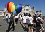 Activists walk past a large rainbow-colored heart erected in front of the country's parliament building in Budapest, Hungary, on Thursday, July 8, 2021. The activists are protesting against the recently passed law they say discriminates and marginalizes LGBT people. (AP Photo/Laszlo Balogh)