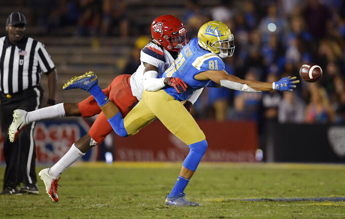 UCLA tight end Caleb Wilson, right, can't reach a pass while under pressure from Arizona safety Demetrius Flannigan-Fowles during the second half of an NCAA college football game Saturday, Oct. 20, 2018, in Pasadena, Calif. UCLA won 31-30. (AP Photo/Mark J. Terrill)