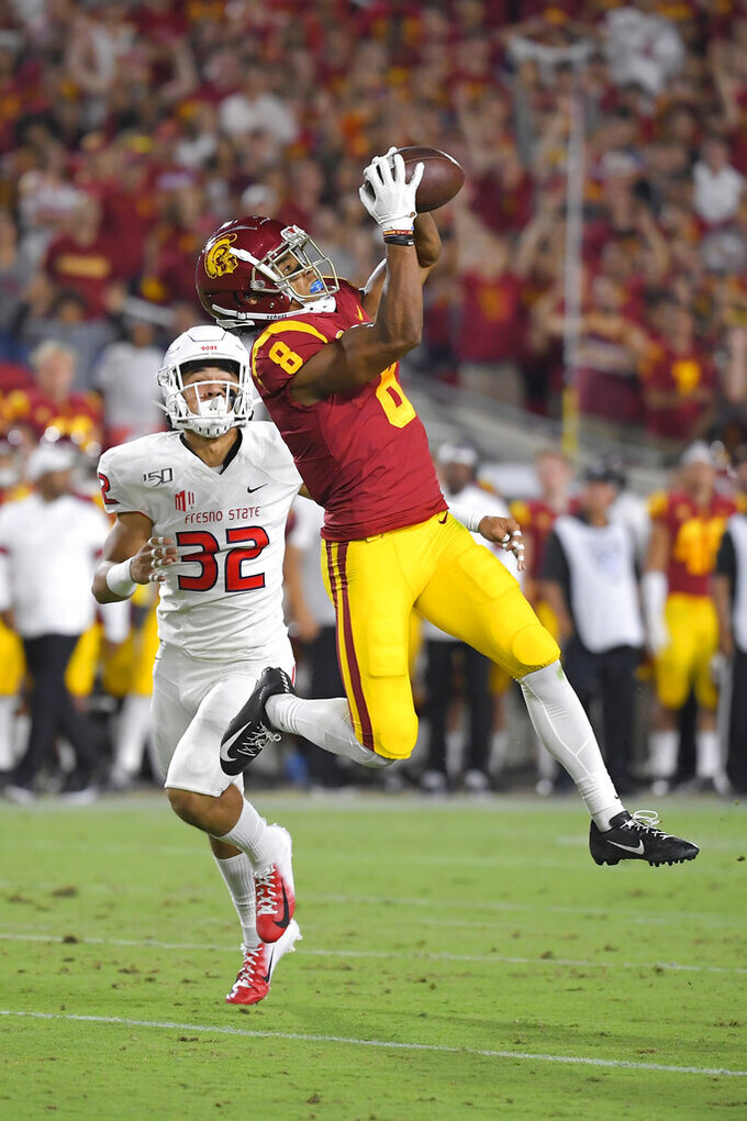Southern California wide receiver Amon-Ra St. Brown, right, makes a catch as Fresno State defensive back Evan Williams watches during the first half of an NCAA college football game Saturday, Aug. 31, 2019, in Los Angeles. The catch was called back due to a penalty against USC. (AP Photo/Mark J. Terrill)
