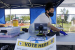 FILE - In this May 12, 2020, file photo, election worker Laura Herrera disinfects her station at a mobile voting site amid the coronavirus pandemic during a special election in Lancaster, Calif. California will establish hundreds of in-person voting places across the state for the November election, even in a year when every registered voter will be sent a mail-in ballot because of health concerns over the coronavirus. Counties must have at least one voting location per 10,000 registered voters. Statewide mail-in voting has been criticized by national Republicans as a possible pathway to large-scale voter fraud.(AP Photo/Marcio Jose Sanchez, File)