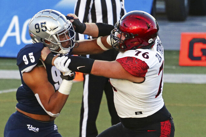 Nevada, lieman Tristan Nichols (95) left, and San Diego St defensive lineman Thomas Zachary (76) battle each other in the second half of an NCAA college football game Saturday, Nov. 21, 2020, in Reno, Nev. (AP Photo/Lance Iversen)